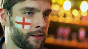 Αρσενικός οπαδός ποδοσφαίρου με την αγγλική σημαία στο μάγουλο που ανατρέπεται για την αγαπημένη απώλεια ομάδων απόθεμα βίντεο