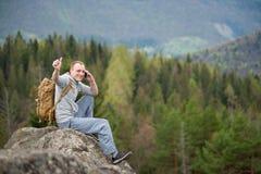 Αρσενικός ορειβάτης με το καφετί σακίδιο πλάτης στην αιχμή του βράχου Στοκ φωτογραφία με δικαίωμα ελεύθερης χρήσης