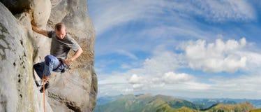 Αρσενικός ορειβάτης που αναρριχείται στο μεγάλο λίθο στη φύση με το σχοινί Στοκ φωτογραφία με δικαίωμα ελεύθερης χρήσης