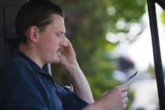 Αρσενικός οδηγός που καλεί με τηλέφωνο κυττάρων με τις σημειώσεις διαθέσιμες Στοκ Εικόνα