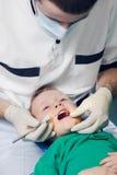 Αρσενικός οδοντίατρος που εξετάζει τα δόντια αγοριών Στοκ Εικόνες