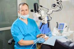 Αρσενικός οδοντίατρος που εργάζεται με το μικροσκόπιο στη σύγχρονη κλινική οδοντιάτρων Στοκ Φωτογραφίες