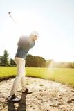 Αρσενικός παίκτης γκολφ που χτυπά τη σφαίρα από μια παγίδα άμμου Στοκ εικόνες με δικαίωμα ελεύθερης χρήσης