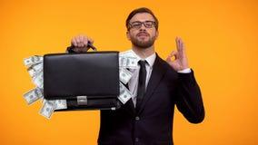 Αρσενικός παρουσιάζοντας χαρτοφύλακας με τα χρήματα και να κάνει την εντάξει χειρονομία, payday δανείζοντας υπηρεσία στοκ φωτογραφία με δικαίωμα ελεύθερης χρήσης