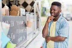 Αρσενικός πελάτης που εξετάζει τον πίνακα διαφημίσεων στο φορτηγό τροφίμων Στοκ Εικόνες