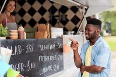 Αρσενικός πελάτης που εξετάζει τον πίνακα διαφημίσεων στο φορτηγό τροφίμων Στοκ Εικόνα