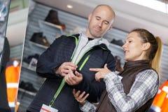 Αρσενικός πελάτης που εξετάζει το χειμερινό παλτό αγοράς Στοκ φωτογραφία με δικαίωμα ελεύθερης χρήσης