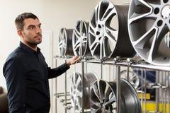 Αρσενικός πελάτης που επιλέγει τα πλαίσια ροδών στην υπηρεσία αυτοκινήτων Στοκ Εικόνες