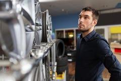 Αρσενικός πελάτης που επιλέγει τα πλαίσια ροδών στην υπηρεσία αυτοκινήτων Στοκ Φωτογραφία
