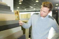 Αρσενικός πελάτης που επιλέγει το λινέλαιο μπουλονιών στο εσωτερικό κατάστημα Στοκ εικόνα με δικαίωμα ελεύθερης χρήσης