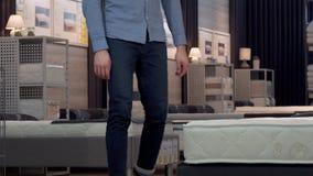 Αρσενικός πελάτης που επιλέγει το ορθοπεδικά στρώμα και το κρεβάτι στο κατάστημα επίπλων απόθεμα βίντεο
