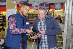 Αρσενικός πελάτης στο κατάστημα υλικού με τον πωλητή Στοκ εικόνες με δικαίωμα ελεύθερης χρήσης
