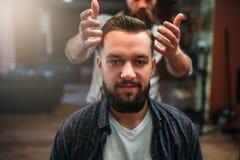 Αρσενικός πελάτης μετά από να κάνει hairstyle στο barbershop Στοκ Εικόνες
