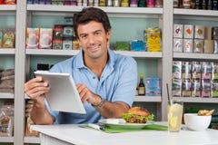 Αρσενικός πελάτης με τα πρόχειρα φαγητά που χρησιμοποιούν την ψηφιακή ταμπλέτα μέσα Στοκ εικόνες με δικαίωμα ελεύθερης χρήσης