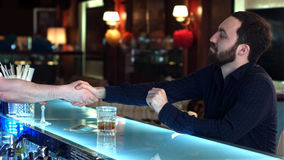 Αρσενικός πελάτης με τα χρήματα μετρητών που πληρώνει για το κοκτέιλ στο φραγμό Στοκ Εικόνες