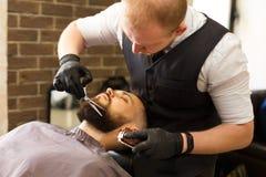 Αρσενικός πελάτης που έχει το κούρεμα γενειάδων στο barbershop Στοκ Φωτογραφία