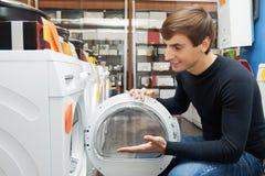 Αρσενικός πελάτης που εξετάζει τα πλυντήρια και τους στεγνωτήρες Στοκ φωτογραφία με δικαίωμα ελεύθερης χρήσης