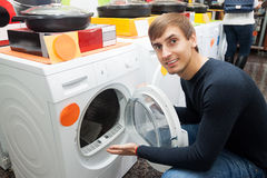 Αρσενικός πελάτης που εξετάζει τα πλυντήρια και τους στεγνωτήρες Στοκ Φωτογραφία