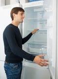 Αρσενικός πελάτης που εξετάζει τα σύγχρονα ψυγεία Στοκ Εικόνες