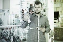 Αρσενικός πελάτης που εξετάζει τους διάφορους σωλήνες κόλλας στο κατάστημα Στοκ εικόνες με δικαίωμα ελεύθερης χρήσης