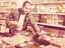 Αρσενικός πελάτης που επιλέγει τα καρύδια και το σιτάρι στο μέσο κατάστημα τροφίμων Στοκ εικόνες με δικαίωμα ελεύθερης χρήσης