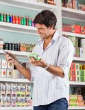 Αρσενικός πελάτης που ελέγχει τον κατάλογο στο κατάστημα Στοκ φωτογραφίες με δικαίωμα ελεύθερης χρήσης
