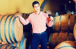 Αρσενικός πελάτης που δοκιμάζει το κόκκινο κρασί από τα ξύλινα βαρέλια Στοκ εικόνα με δικαίωμα ελεύθερης χρήσης