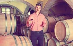 Αρσενικός πελάτης που δοκιμάζει το κόκκινο κρασί από τα ξύλινα βαρέλια Στοκ Εικόνα