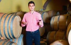 Αρσενικός πελάτης που δοκιμάζει το κόκκινο κρασί από τα ξύλινα βαρέλια Στοκ εικόνες με δικαίωμα ελεύθερης χρήσης