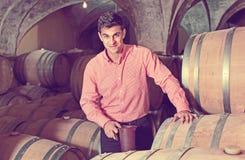 Αρσενικός πελάτης που δοκιμάζει το κόκκινο κρασί από τα ξύλινα βαρέλια Στοκ Εικόνες