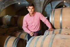 Αρσενικός πελάτης που δοκιμάζει το κόκκινο κρασί από τα ξύλινα βαρέλια Στοκ Φωτογραφίες