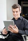 Αρσενικός πελάτης που χρησιμοποιεί την ψηφιακή ταμπλέτα στο σαλόνι Στοκ φωτογραφία με δικαίωμα ελεύθερης χρήσης