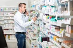 Αρσενικός πελάτης που χρησιμοποιεί το κινητό τηλέφωνο και ψηφιακός Στοκ εικόνες με δικαίωμα ελεύθερης χρήσης