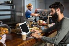 Αρσενικός πελάτης που χρησιμοποιεί το lap-top ενώ έχοντας τον καφέ στο μετρητή Στοκ φωτογραφίες με δικαίωμα ελεύθερης χρήσης