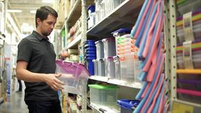Αρσενικός πελάτης στο κατάστημα Αυτός που παίρνει το πλαστικό εμπορευματοκιβώτιο από το ράφι απόθεμα βίντεο