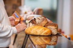 Αρσενικός πελάτης τα ψωμιά που τοποθετούνται με στο μετρητή Στοκ Εικόνες