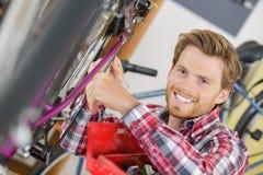 Αρσενικός ποδηλάτης που επισκευάζει το ποδήλατο βουνών Στοκ Εικόνες