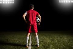Αρσενικός ποδοσφαιριστής που στέκεται στο στάδιο με μια σφαίρα Στοκ Εικόνες