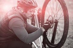 Αρσενικός ποδηλάτης βουνών που εξετάζει την μπροστινή ρόδα του ποδηλάτου του Στοκ εικόνα με δικαίωμα ελεύθερης χρήσης