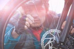 Αρσενικός ποδηλάτης βουνών που εξετάζει την μπροστινή ρόδα του ποδηλάτου του Στοκ φωτογραφία με δικαίωμα ελεύθερης χρήσης