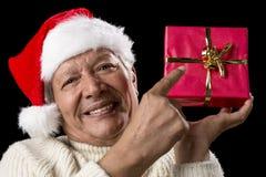 Αρσενικός πρεσβύτερος που δείχνει στο κόκκινο τυλιγμένο δώρο Χριστουγέννων στοκ φωτογραφία