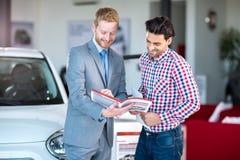 Αρσενικός πωλητής και αρσενικός πελάτης στην αίθουσα εμποριών αυτοκινήτων Στοκ φωτογραφία με δικαίωμα ελεύθερης χρήσης