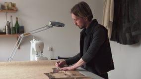 Αρσενικός ράφτης που δημιουργεί το σχέδιο ιματισμού εργαζόμενος στον εργασιακό χώρο απόθεμα βίντεο