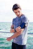 Αρσενικός δρομέας που ακούει τις τοποθετήσεις ρύθμισης μουσικής armband για το smartphone Στοκ Εικόνες