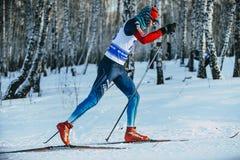 Αρσενικός σκιέρ αθλητών κινηματογραφήσεων σε πρώτο πλάνο κατά τη διάρκεια του δασικού κλασικού ύφους αγώνων Στοκ Εικόνες