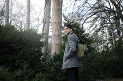 Αρσενικός σπουδαστής hipster με το σακίδιο πλάτης που περπατά μέσω του πάρκου Στοκ Φωτογραφία