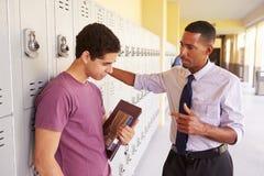 Αρσενικός σπουδαστής γυμνασίου που μιλά στο δάσκαλο από τα ντουλάπια Στοκ εικόνα με δικαίωμα ελεύθερης χρήσης