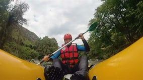 Αρσενικός συγκίνηση-αναζητητής που οδηγά στον τραχύ ποταμό βουνών στο καγιάκ του, που περνά τις πέτρες απόθεμα βίντεο