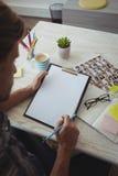 Αρσενικός συντάκτης φωτογραφιών που γράφει στην περιοχή αποκομμάτων στο δημιουργικό γραφείο γραφείων Στοκ εικόνες με δικαίωμα ελεύθερης χρήσης