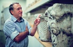 Αρσενικός συνταξιούχος που επισκέπτεται την ιστορική έκθεση στο μουσείο Στοκ Φωτογραφία